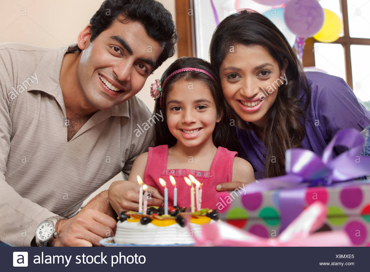 Girl celebrating her birthday with parents - Stock Image