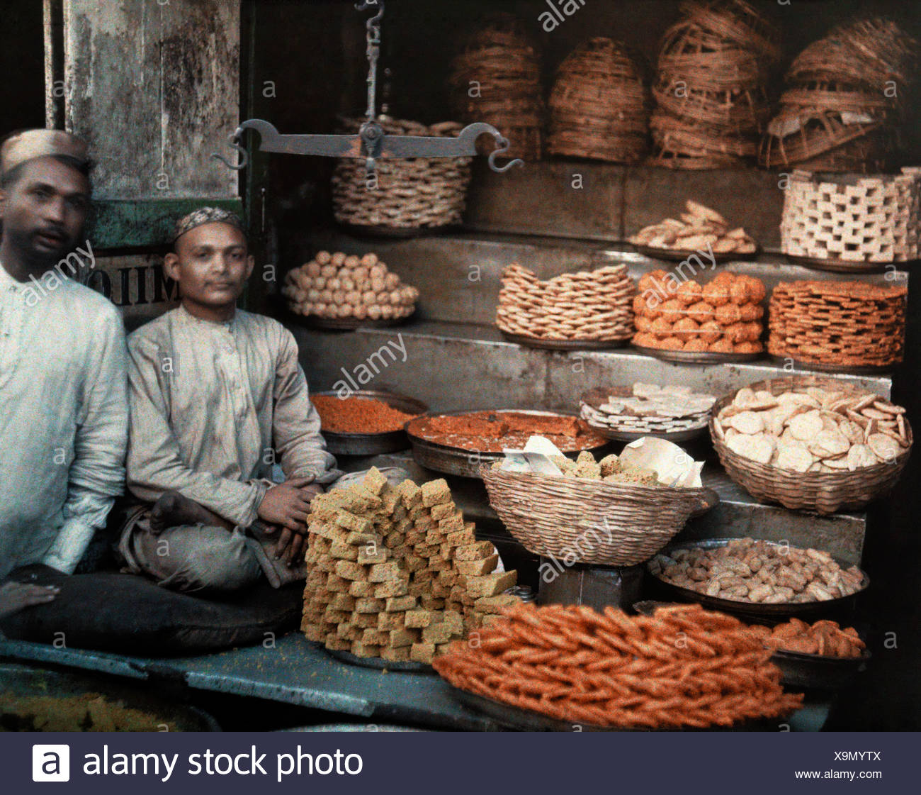 Two merchants sit by their stand of honeycakes in bombay. - Stock Image