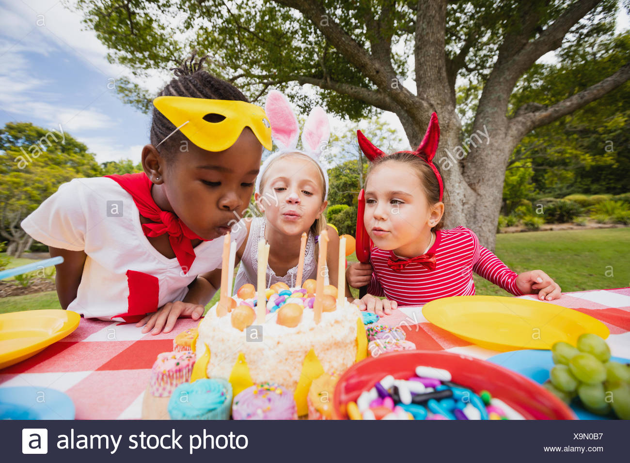 Three little girls blowing together birthday candles Stock Photo