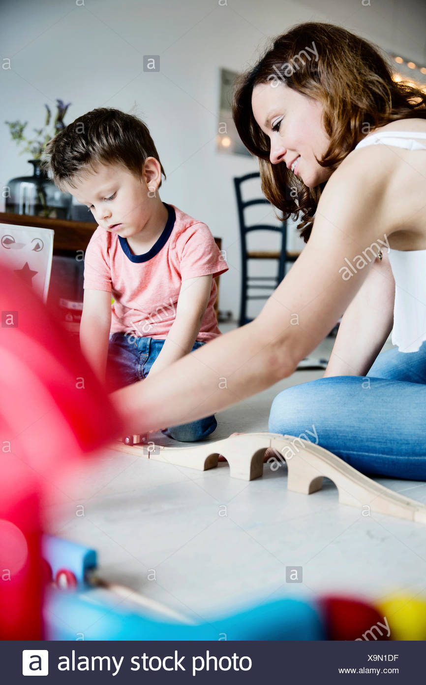 Mother and son plying in living room - Stock Image