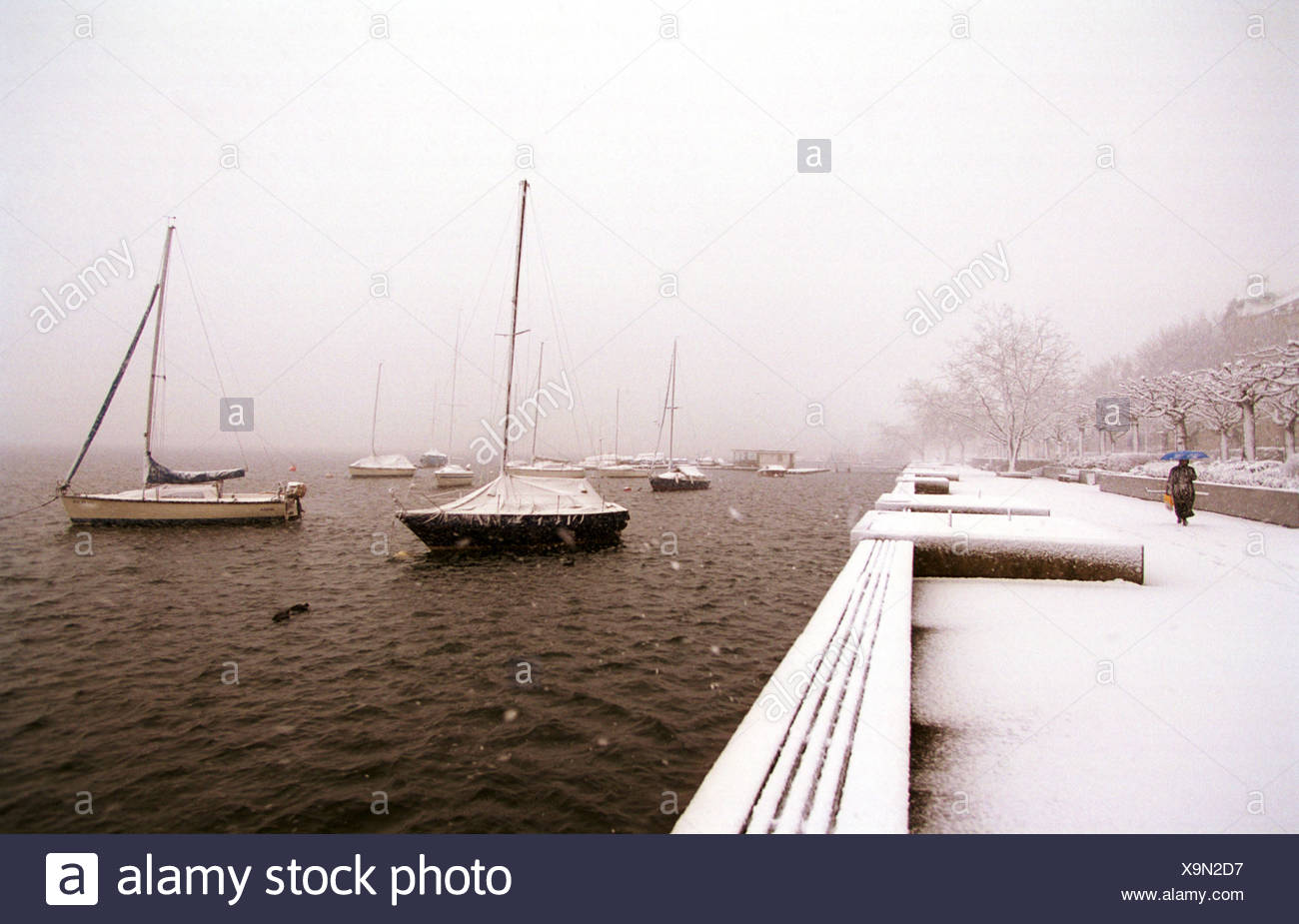 Boats on the snow-covered banks of the Zuerichsees - Stock Image