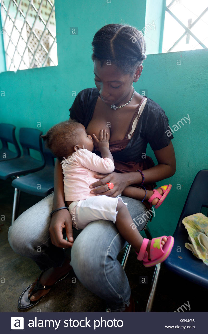 Young mother, 21 years, nursing her daughter, 7 months, kindergarten of the Salesian project Lakou, district of La Saline - Stock Image