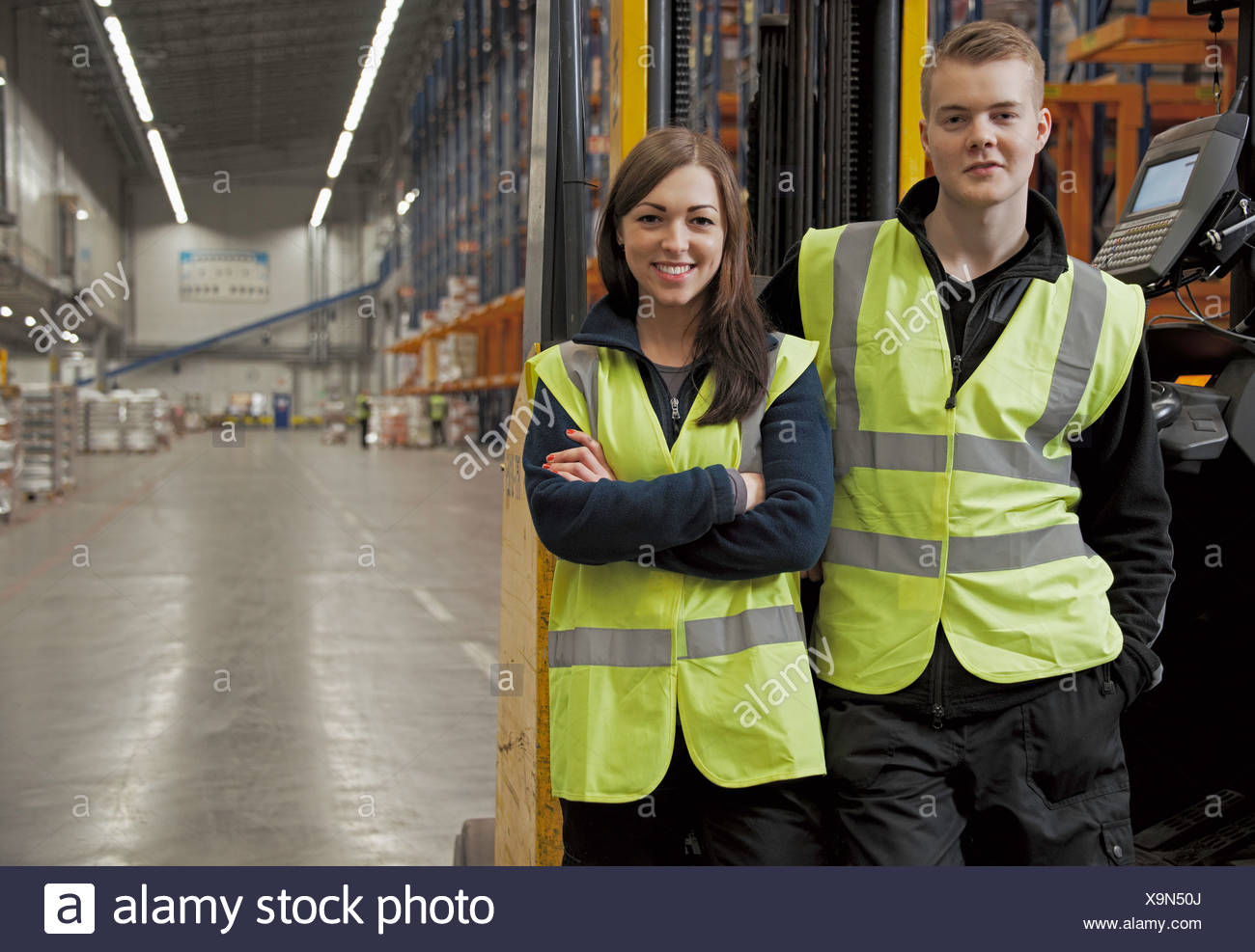 Workers by forklift in warehouse Stock Photo