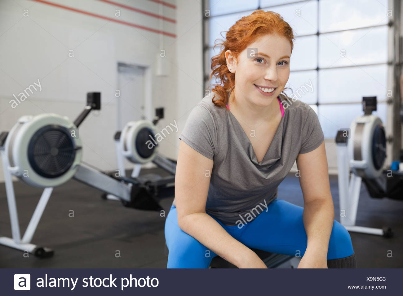 Portrait of woman sitting in gym - Stock Image