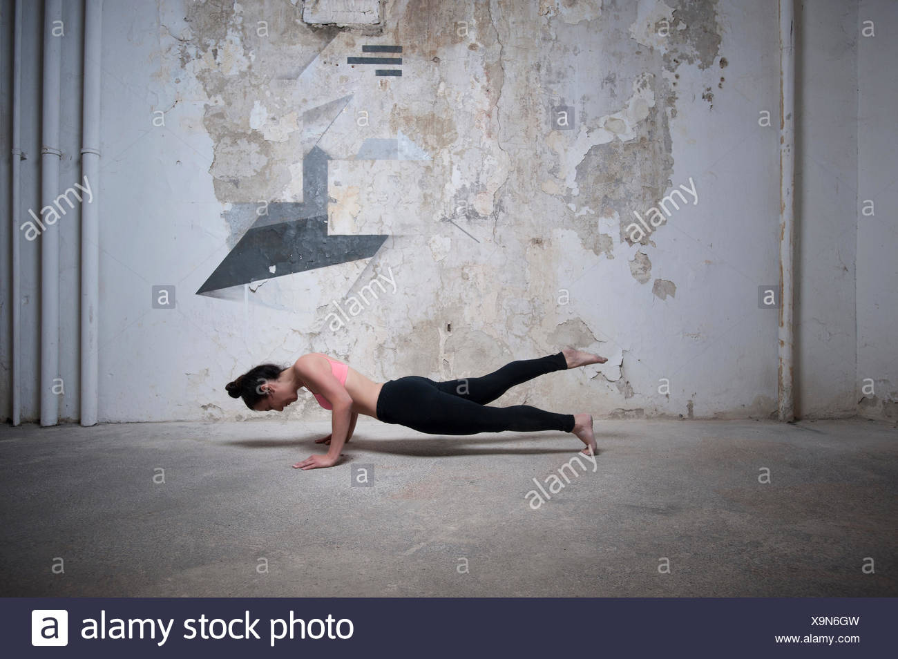 Mid adult woman practicing plank pose in yoga studio, Munich, Bavaria, Germany - Stock Image