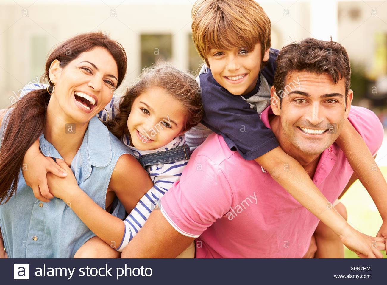 Portrait Of Happy Family In Garden At Home - Stock Image