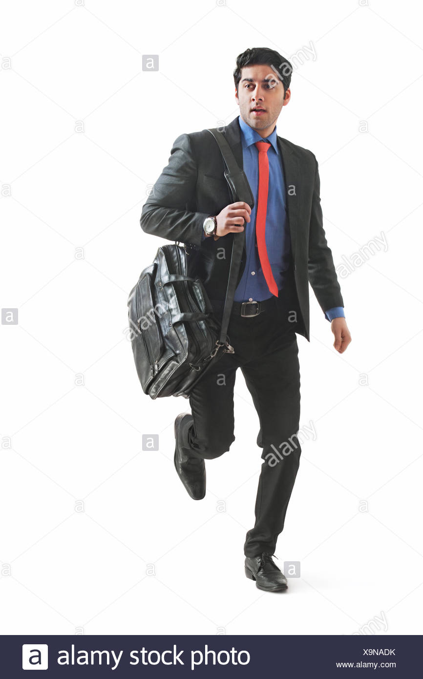 Young businessman holding briefcase and running Stock Photo