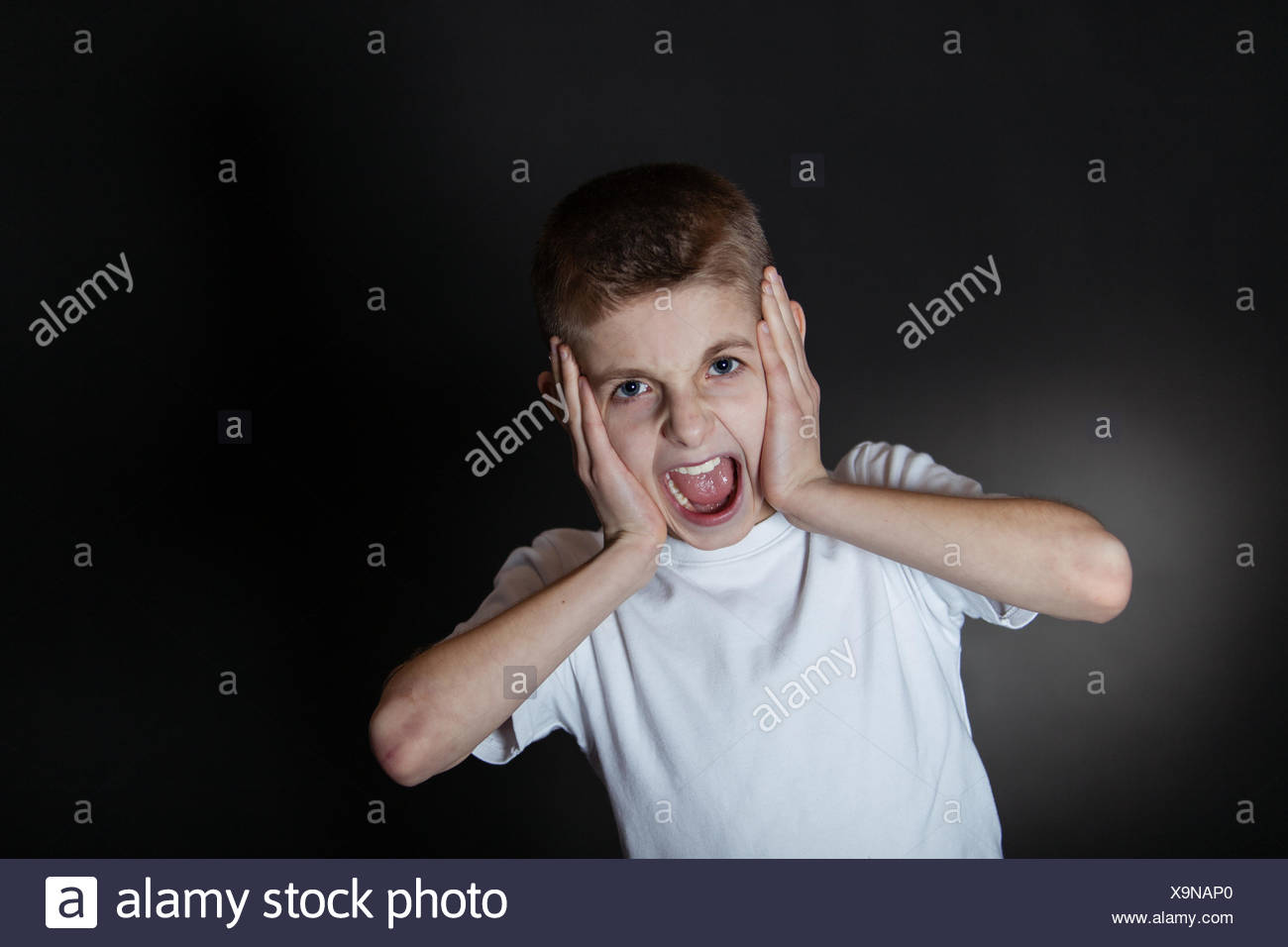 Angry Boy Shouting with Hands Holding on his Face - Stock Image