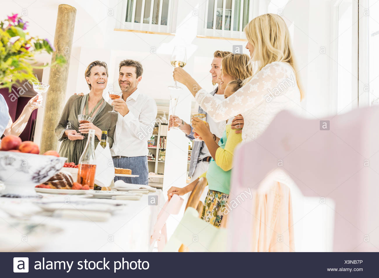 Family raising a toast at dining table - Stock Image