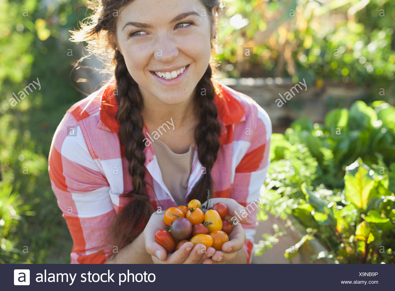 Smiling woman with handful of cherry tomatoes - Stock Image