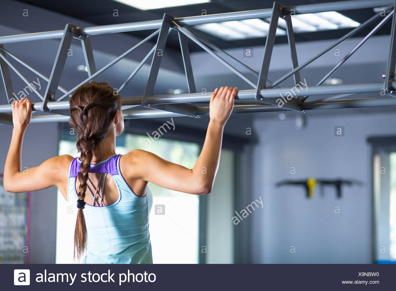 Young woman doing chin ups - Stock Image
