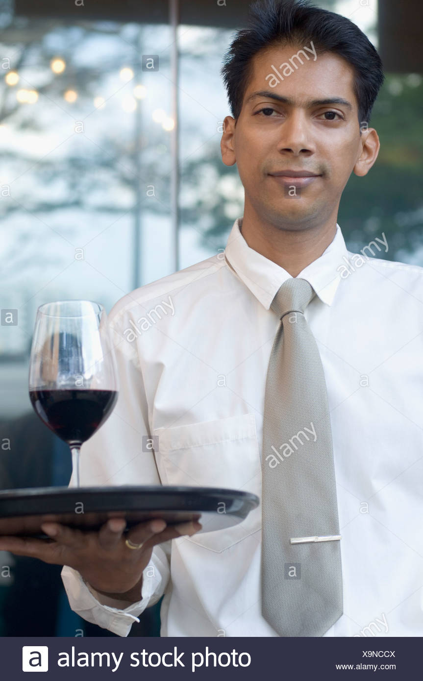 Portrait of a mid adult man holding a glass of red wine on a tray Stock Photo