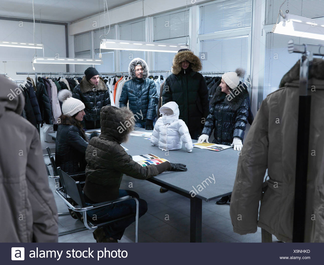 Product developers inspecting coat - Stock Image