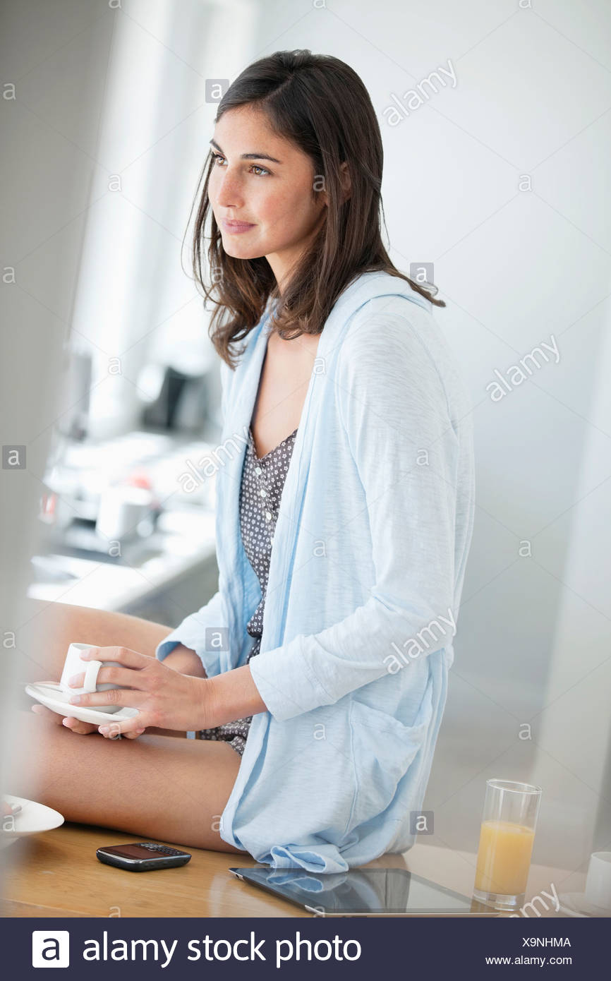 Woman in pajamas drinking coffee - Stock Image