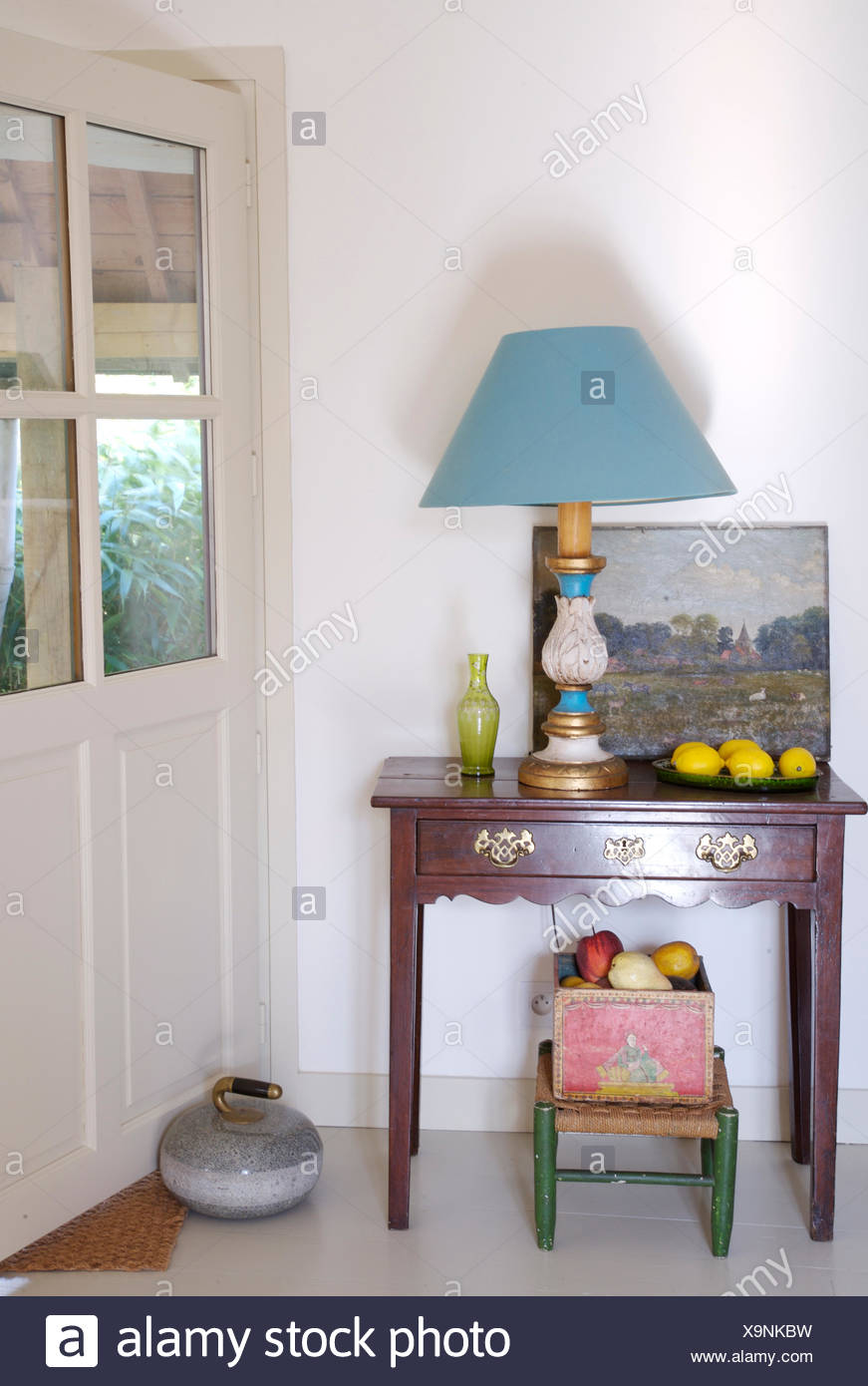 Vintage panting and blue lamp on small antique table in white French country hall - Stock Image
