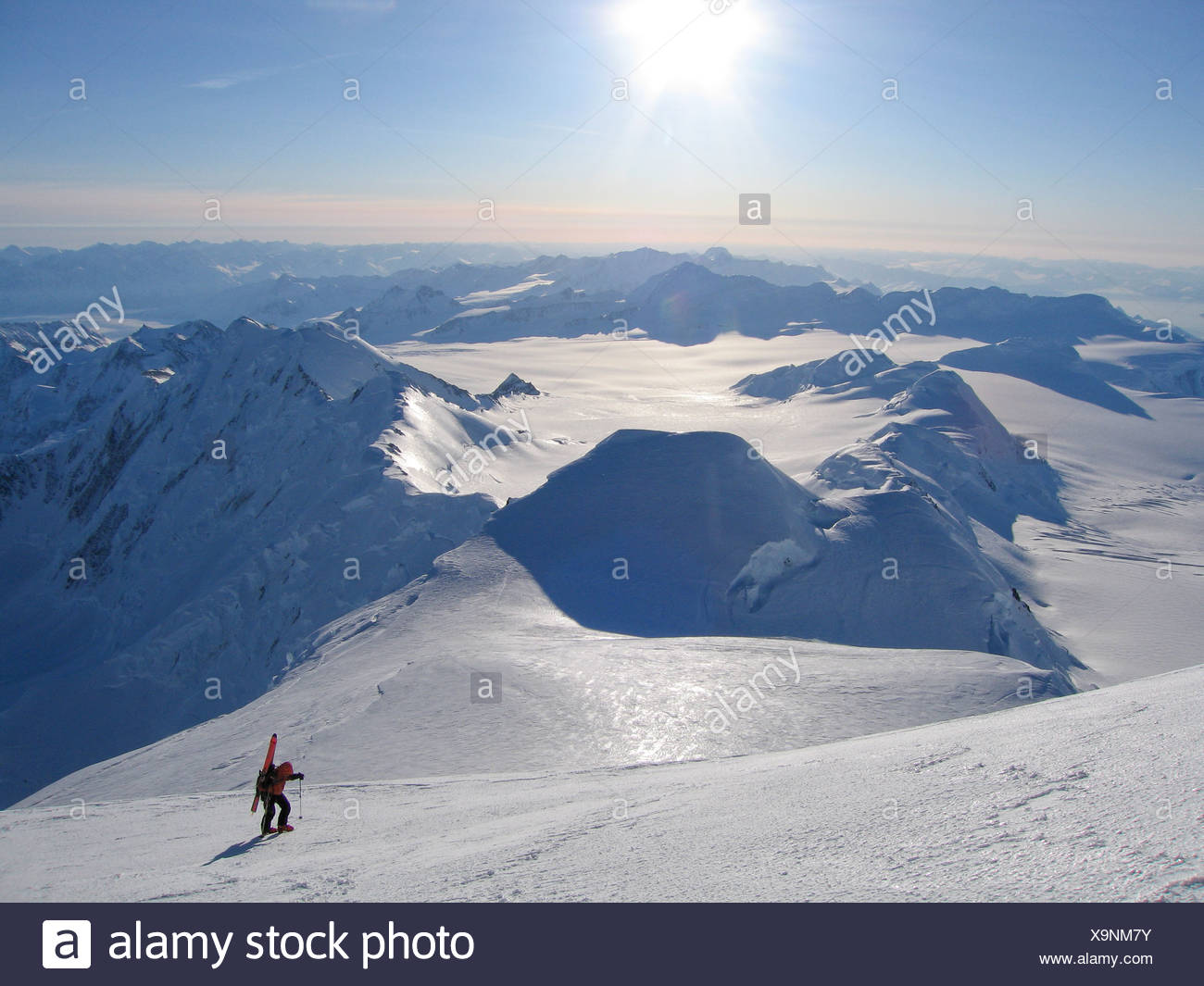 A ski mountaineer ascends the upper reaches of Mount Marcus Baker, the highest peak in the Chugach mountains, in the winter. - Stock Image