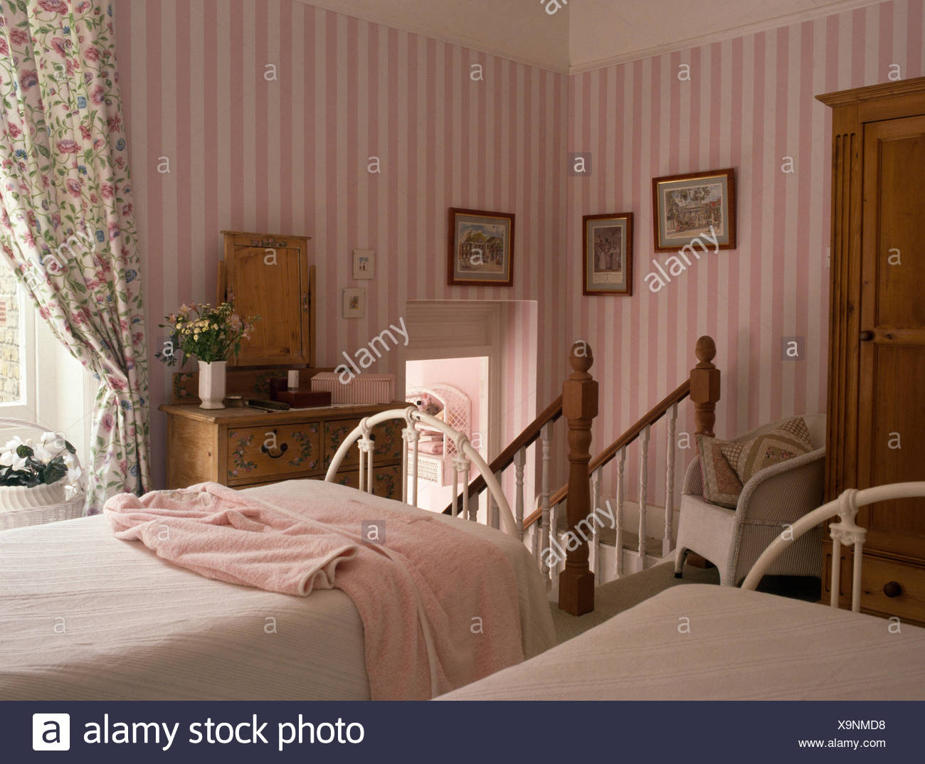 Pink striped wallpaper in country bedroom with white wrought ...