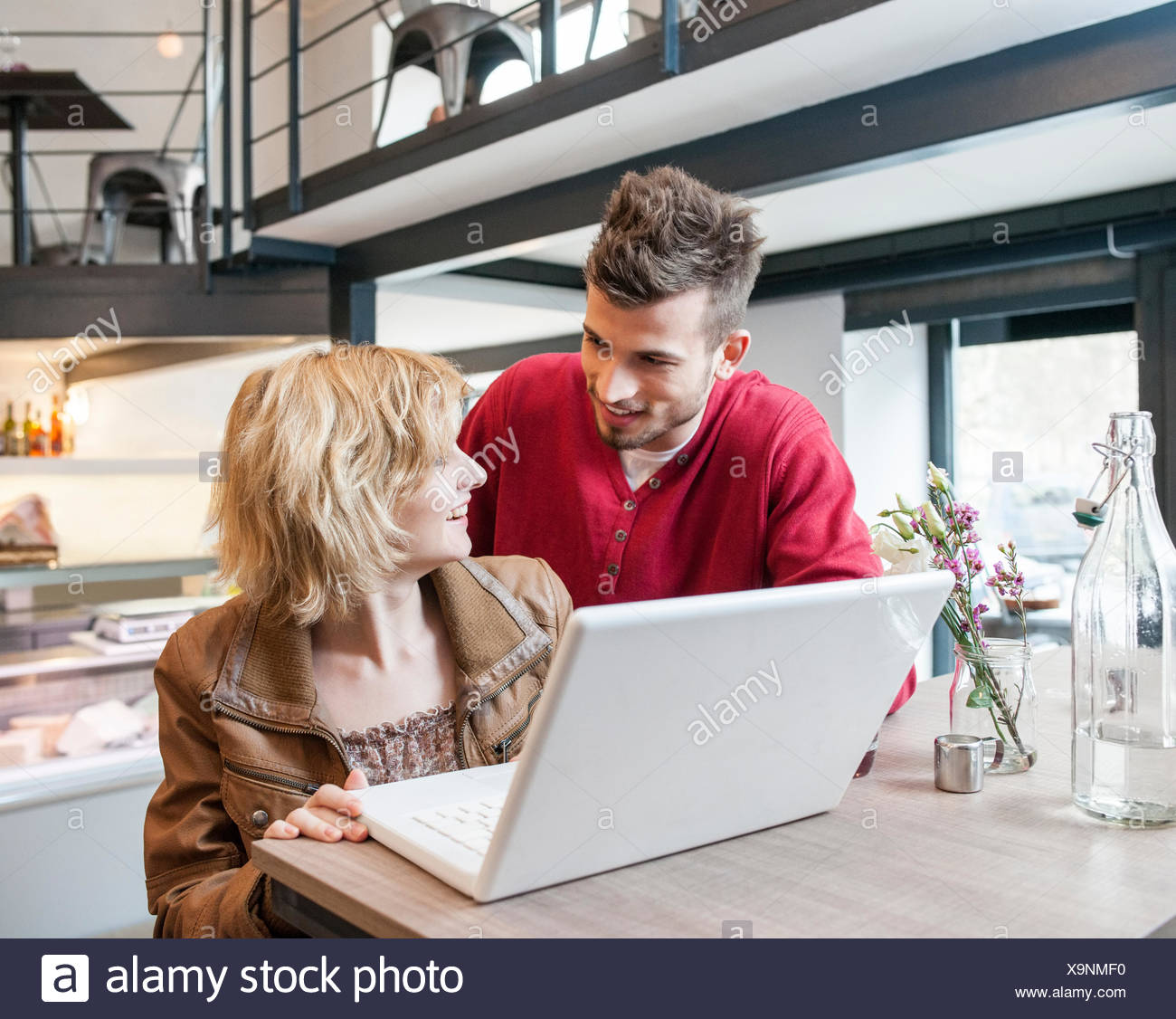 Young couple looking at each other while using laptop in cafe - Stock Image