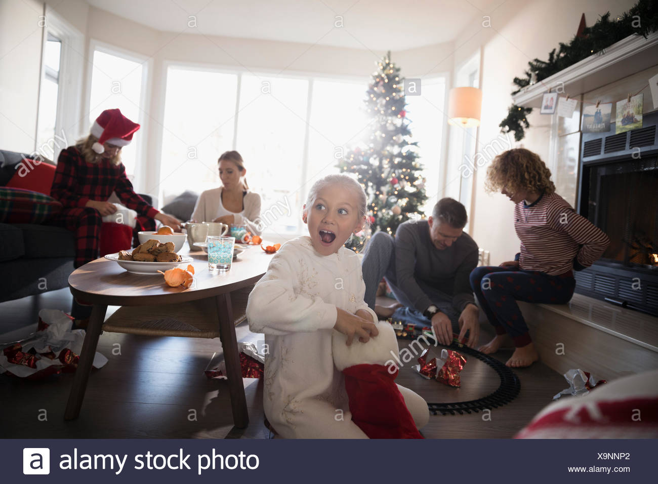 Surprised girl in pajamas opening Christmas stocking with family in living room - Stock Image