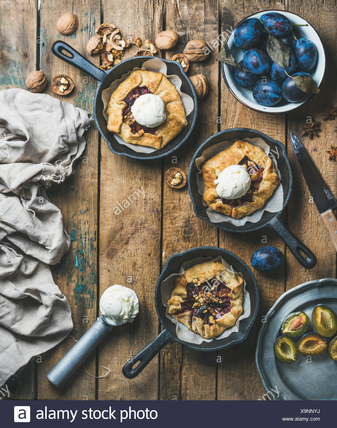 Plum and walnut crostata pie with ice-cream scoops in individual cast iron pans over rustic wooden table, top view, copy space. Slow food concept - Stock Image