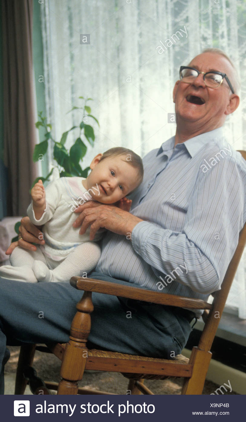 laughing grandpa holding baby in rocking chair - Stock Image