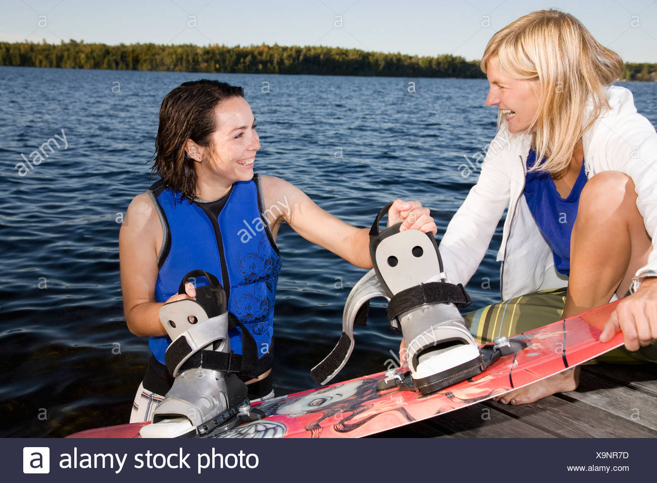 Woman helping friend with wakeboard - Stock Image