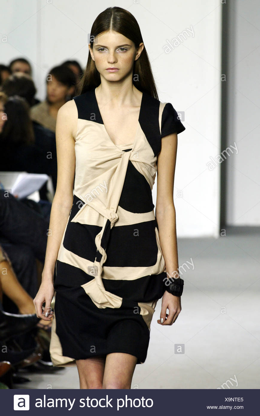 Helmut Lang Paris Ready to Wear Spring Summer Model long brunette hair tucked behind ears wearing black and beige asymmetric - Stock Image
