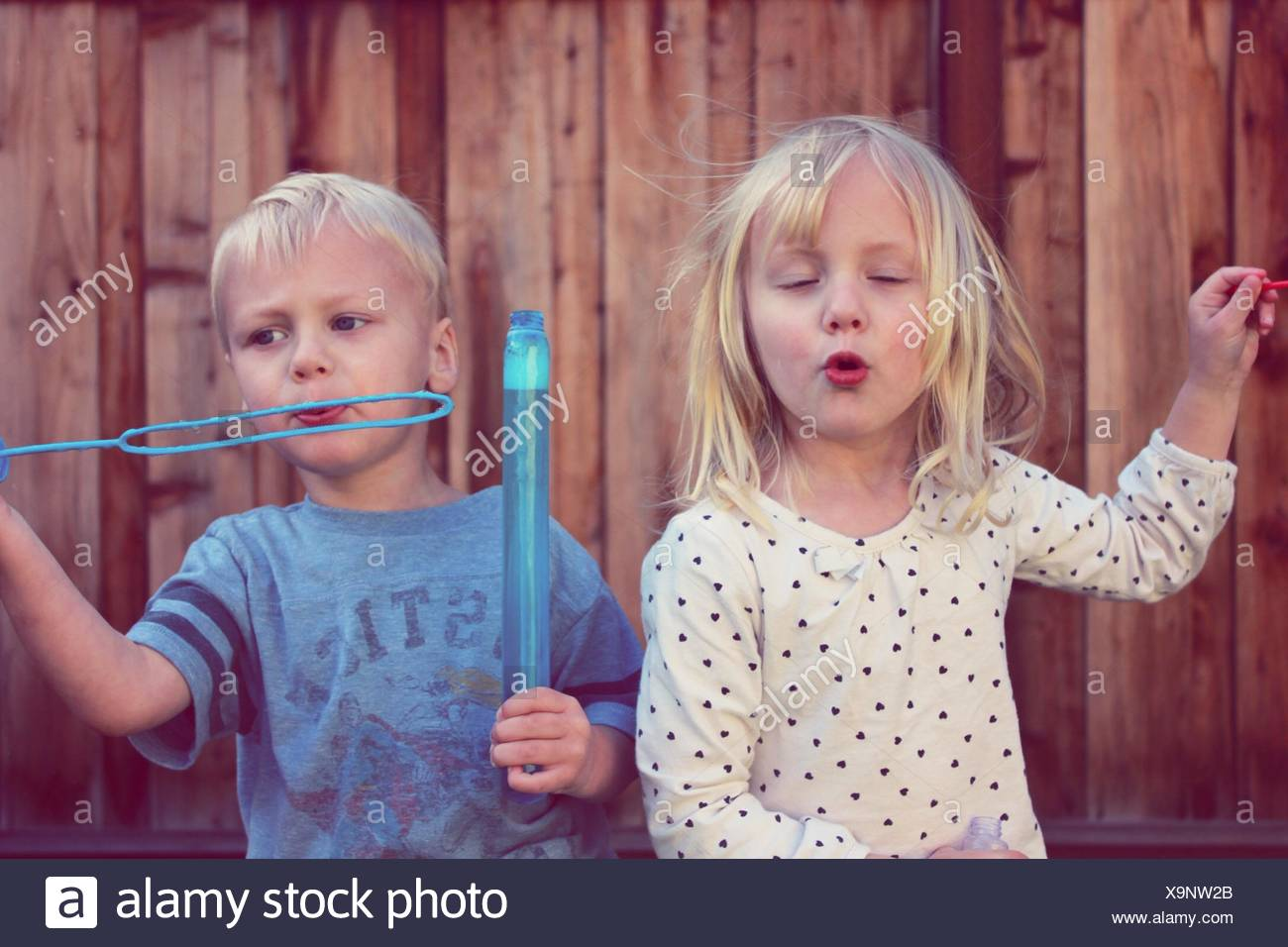 Sibling Playing With Bubbles Backyard - Stock Image