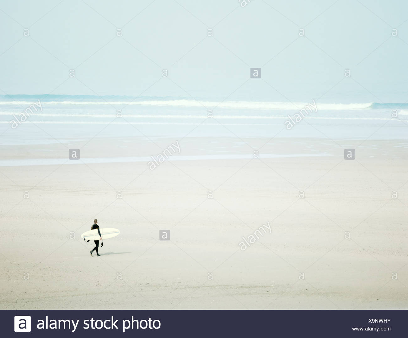 Surfer on beach - Stock Image