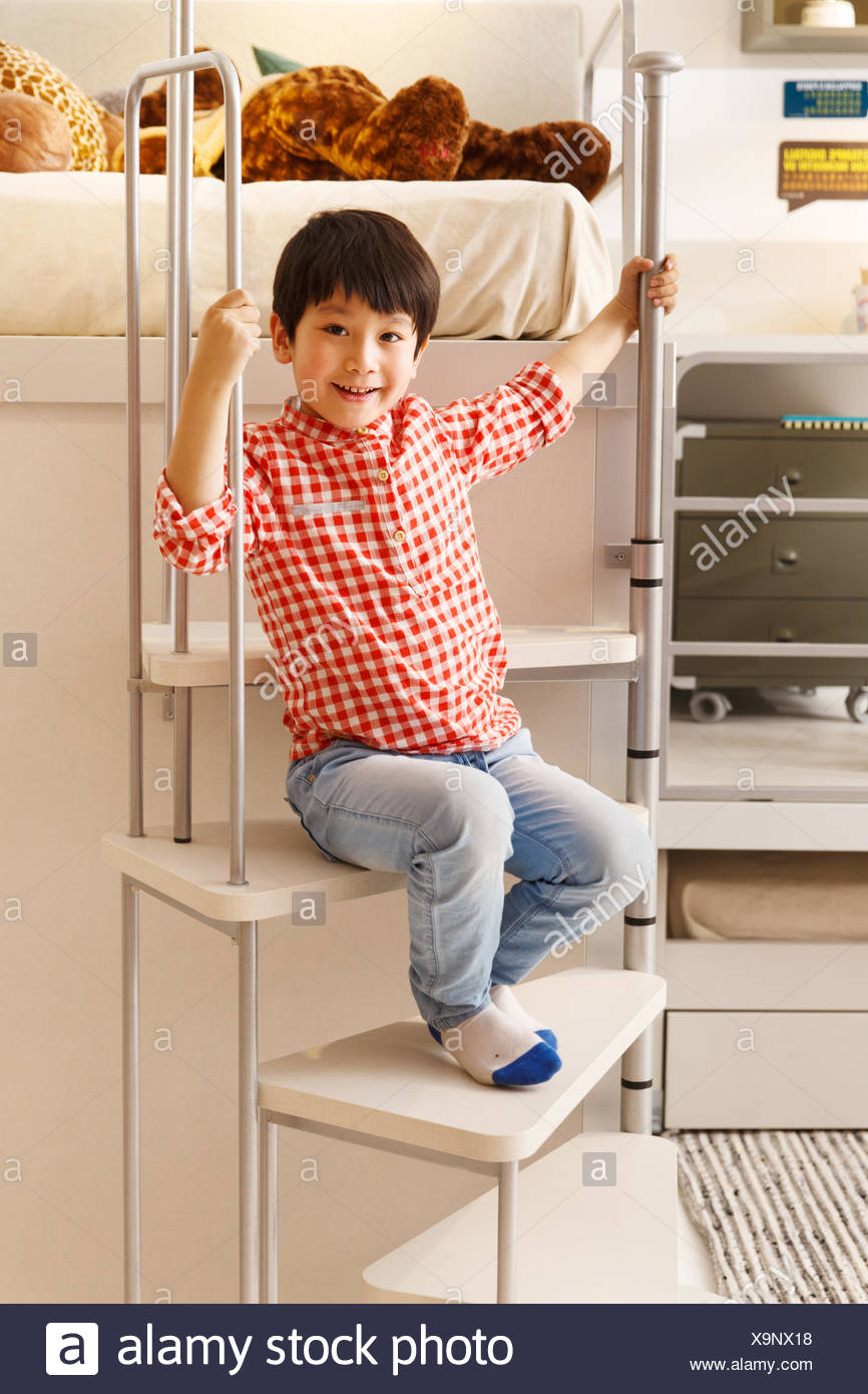 The little boy sat on the steps to play - Stock Image