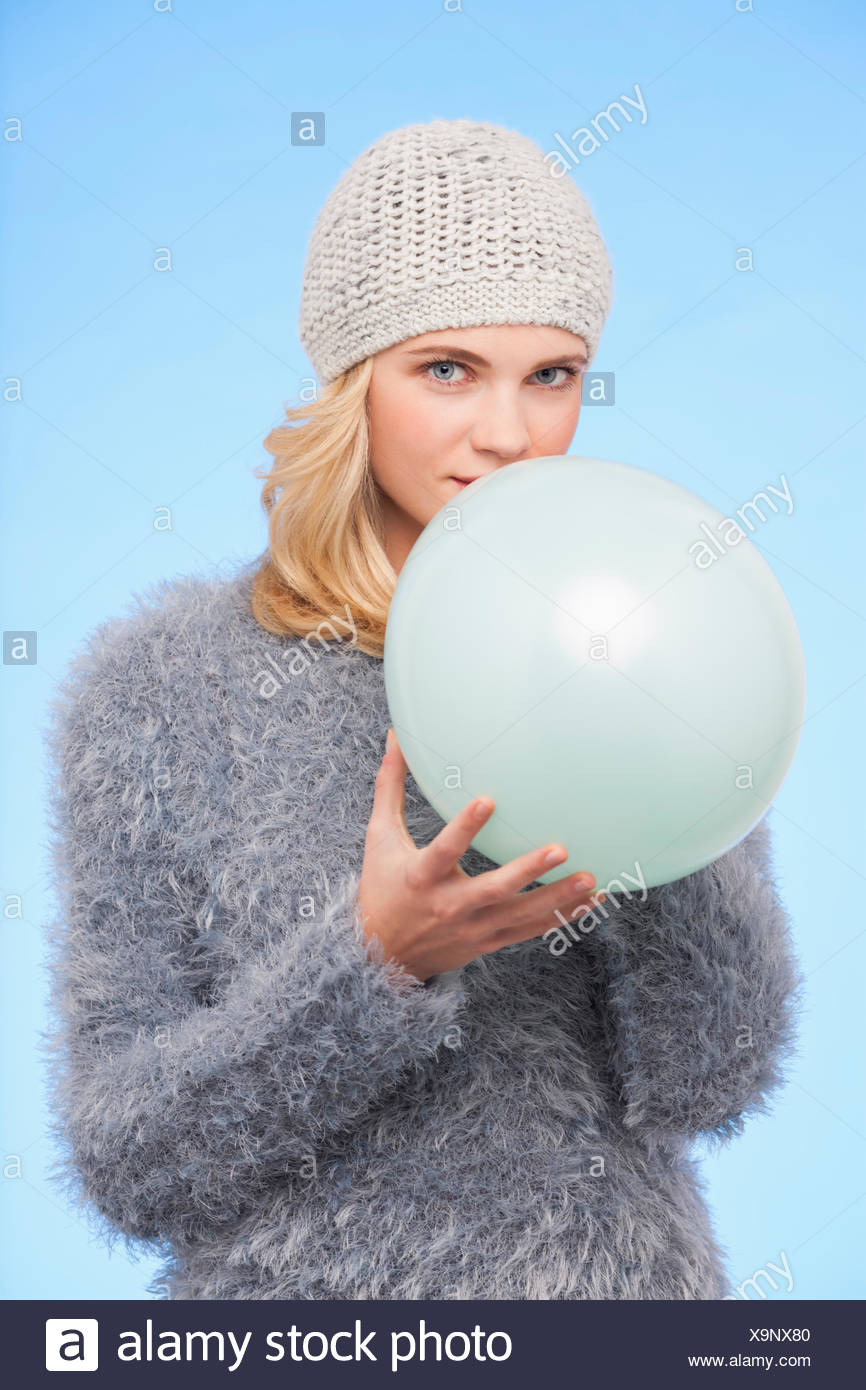 Portrait of a beautiful woman holding balloon in winter - Stock Image
