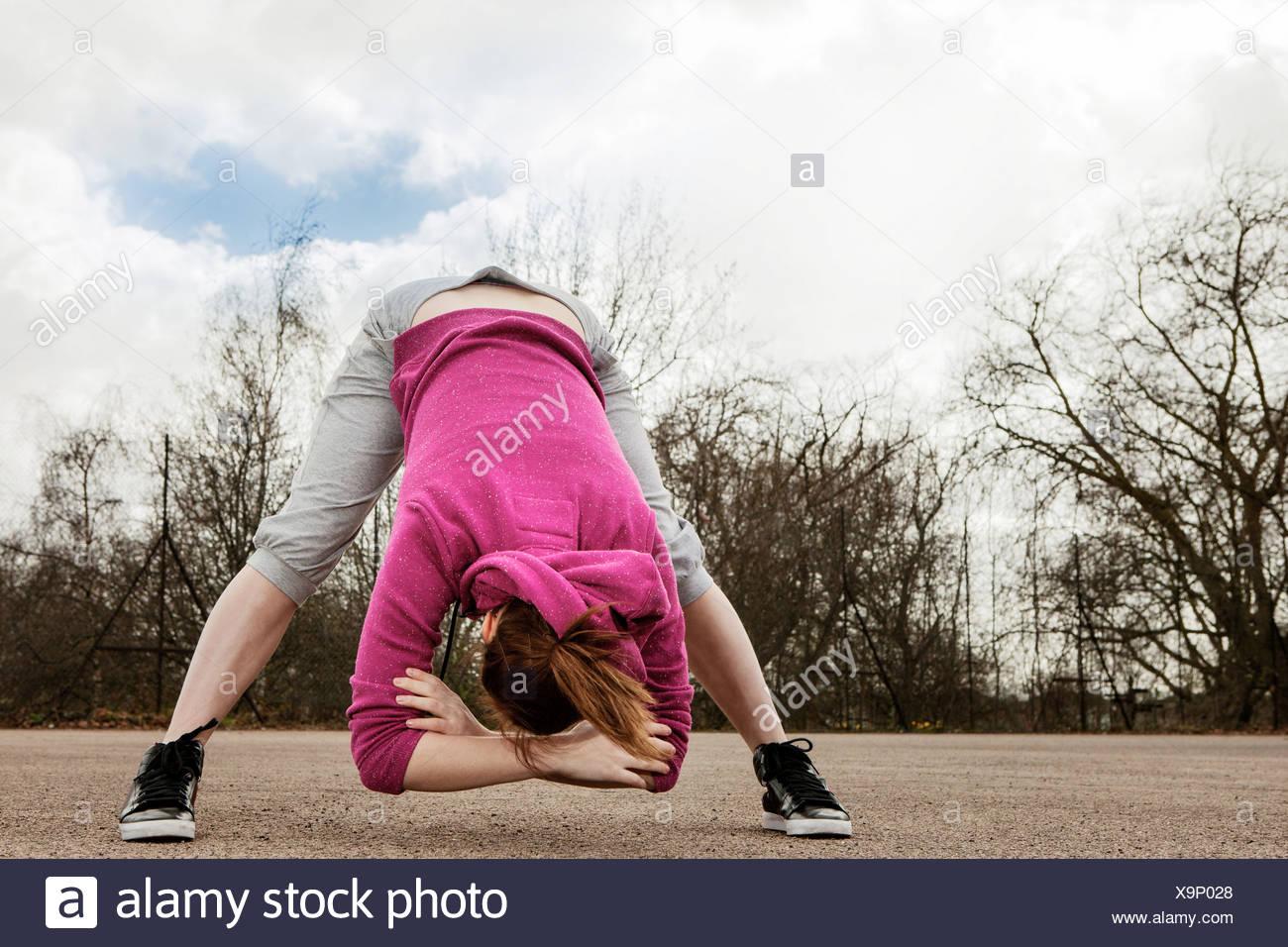 Woman doing bending forward exercise - Stock Image
