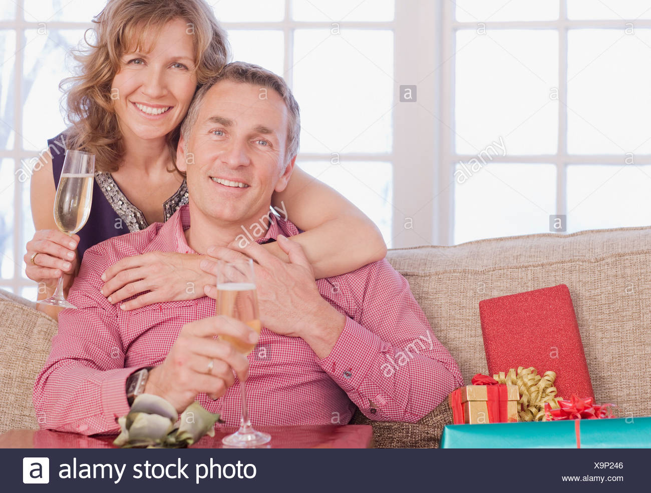 Couple drinking champagne near Christmas gifts Stock Photo