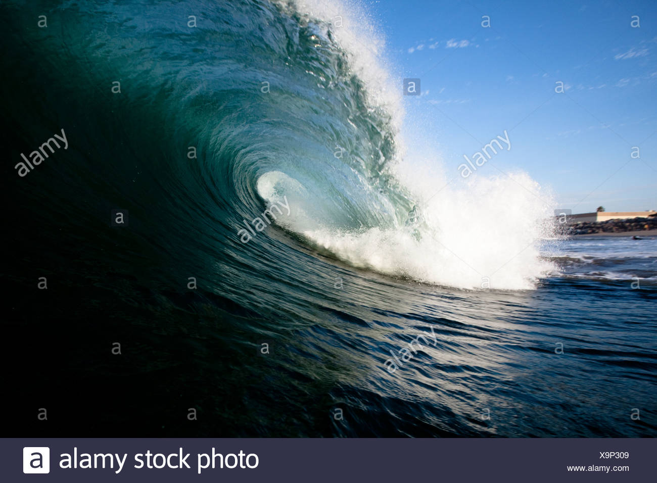 A large wave breaks close to shore. - Stock Image