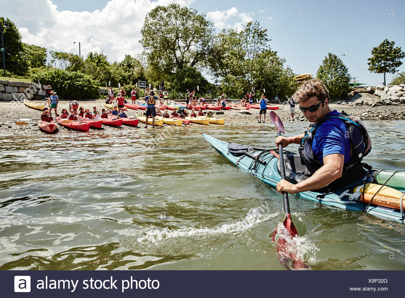 Kayaking instructor paddling in front of students sitting in kayaks, Portland, Maine, USA - Stock Image