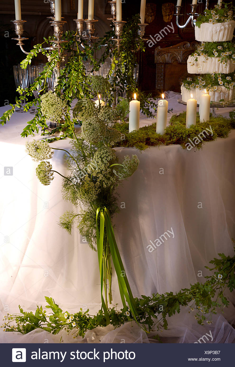 Candles and white Ammi flowers with foliage and flower garland on ...