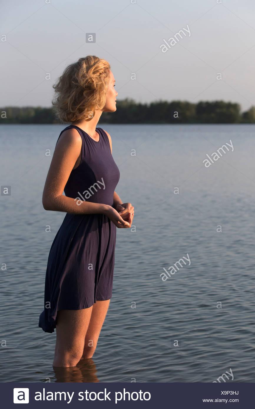 Netherlands, Gelderland, De Rijkerswoerdse Plassen, Beautiful woman standing in lake - Stock Image