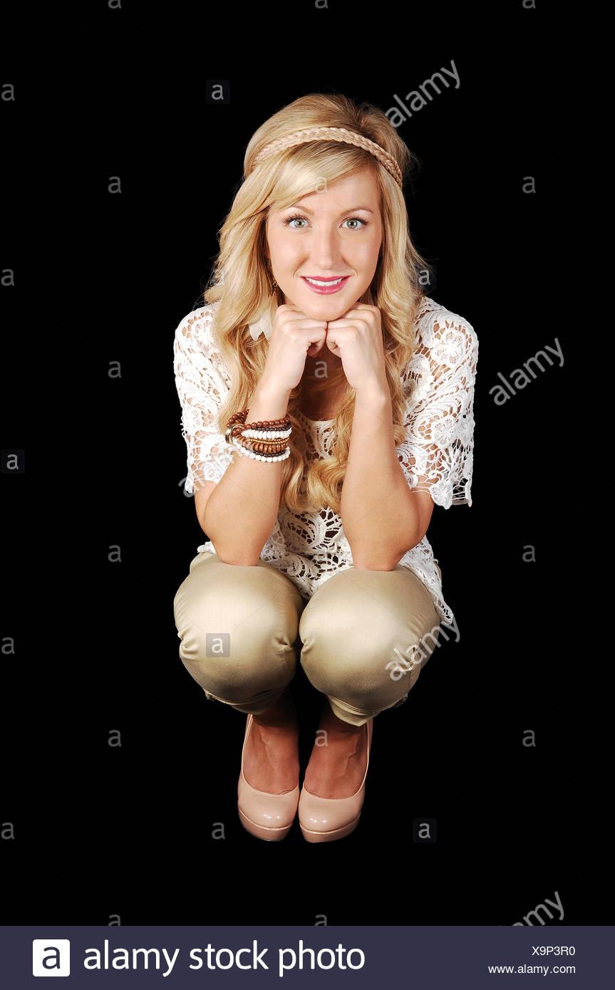 Girl crouching on floor. - Stock Image