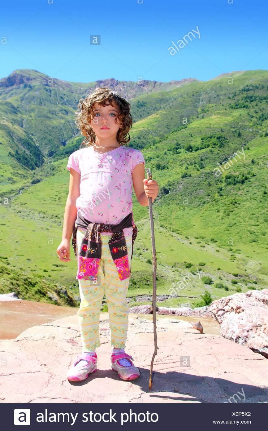 Explorer mountain girl hicker stick cane green valley - Stock Image