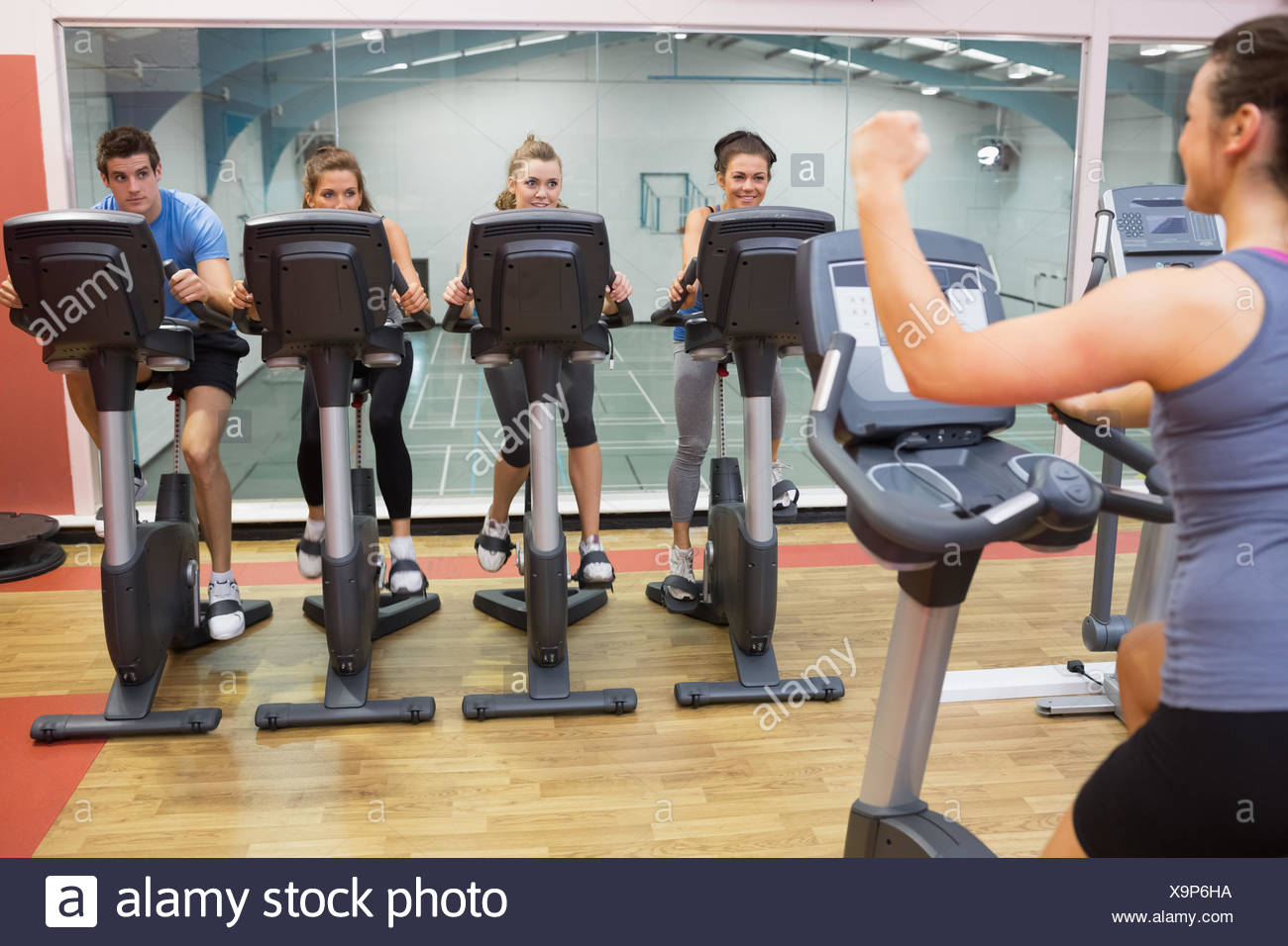 Enthusiastic woman teaching spinning class - Stock Image