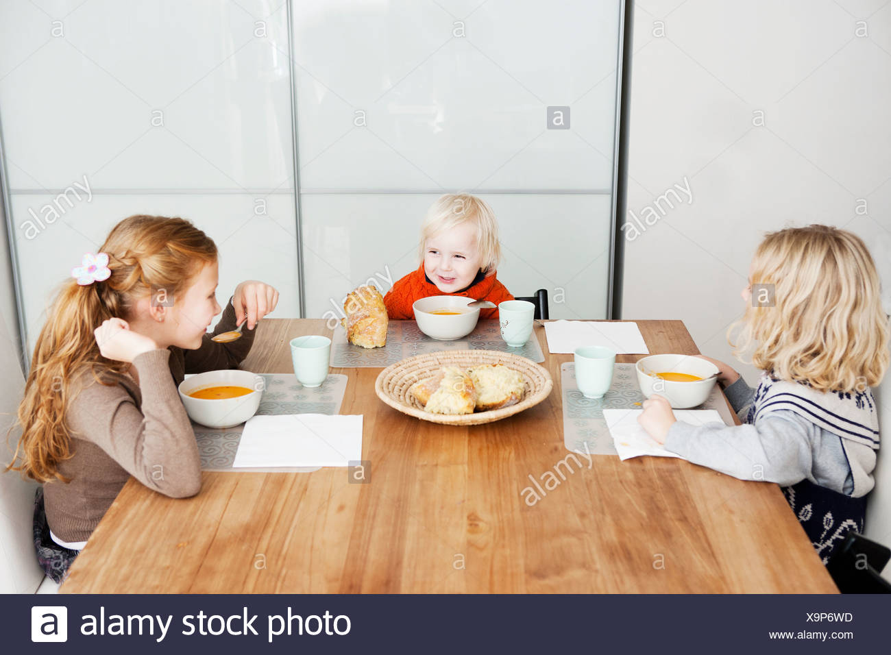 Children eating lunch at table - Stock Image