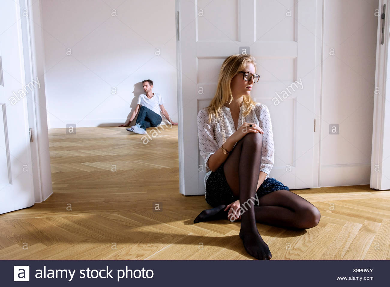 Pensive young woman in empty apartment with man in background - Stock Image