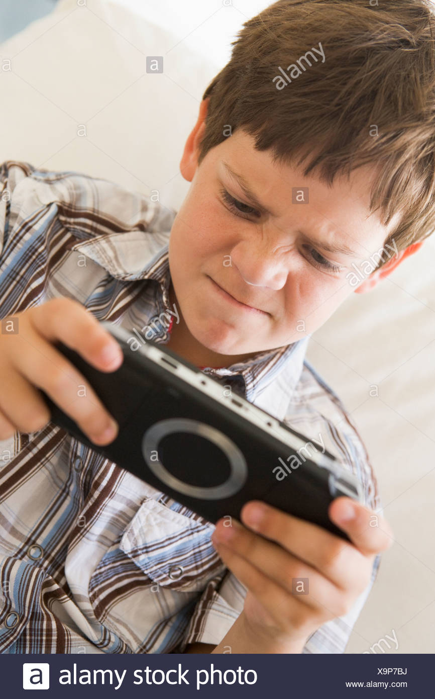 Young boy with handheld game indoors looking unhappy Stock Photo