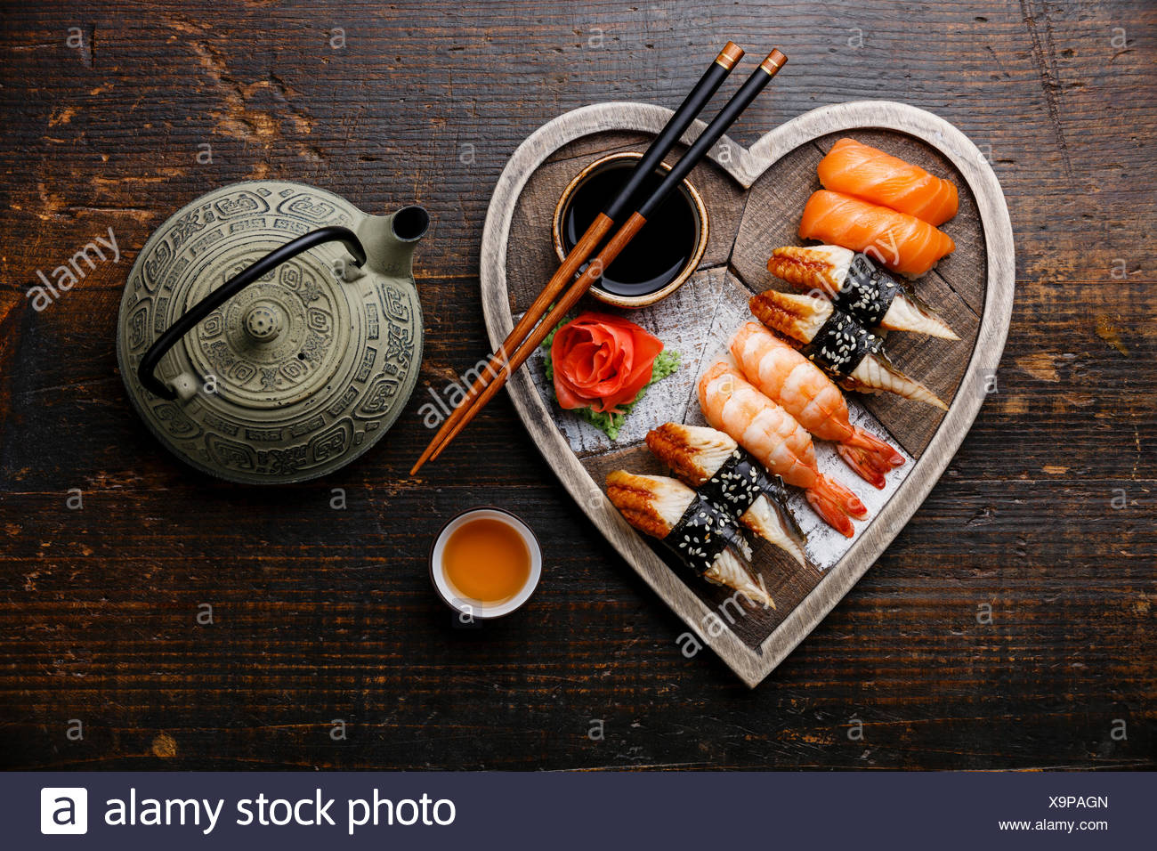 Sushi Set nigiri and tea served on Heart shape wooden tray on dark wooden background - Stock Image