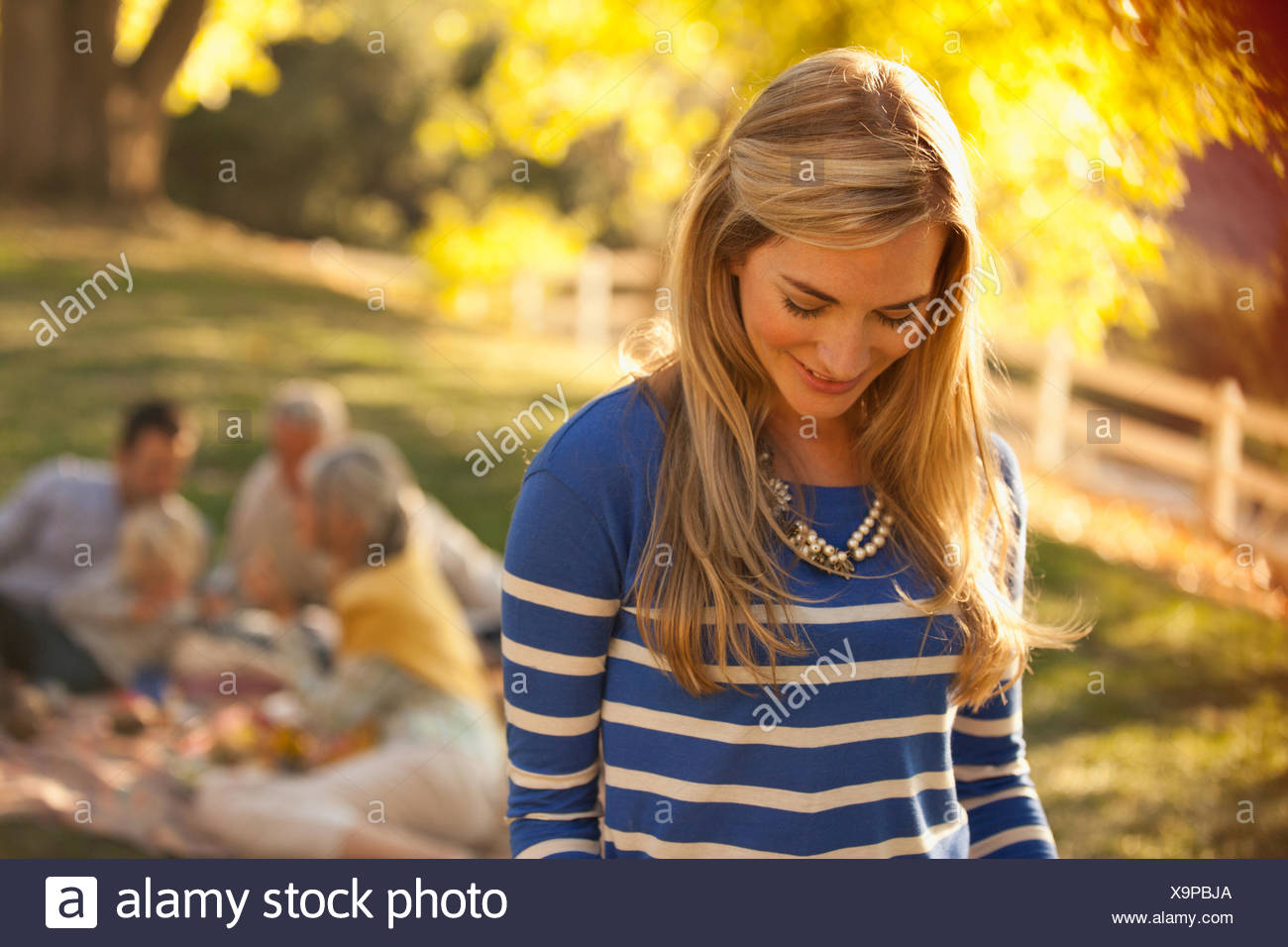 Smiling woman standing outdoors - Stock Image