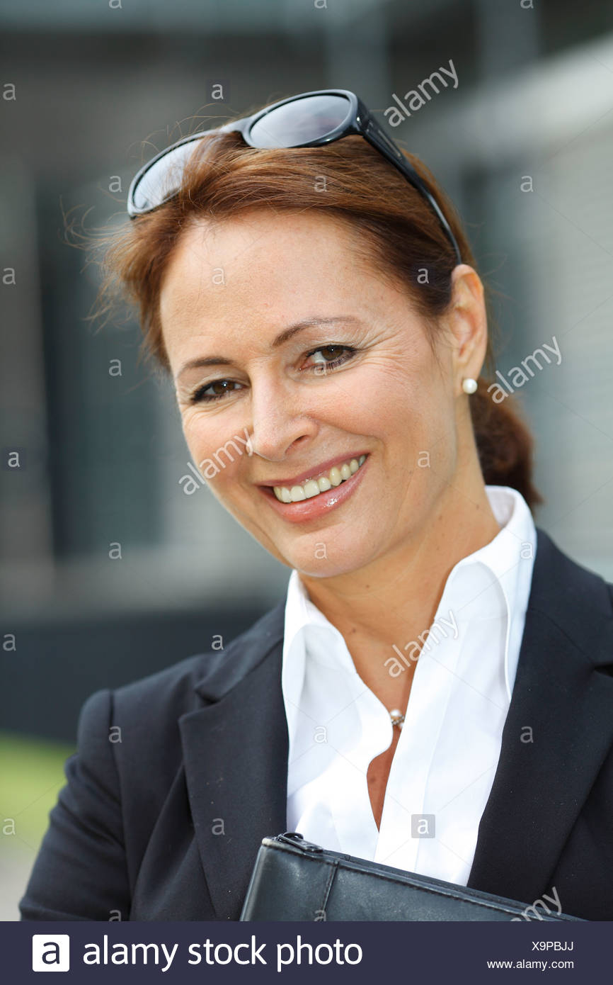 Business woman, years 45, smiling, wearing a lady's suit and carrying a folder, with sunglasses on her head - Stock Image