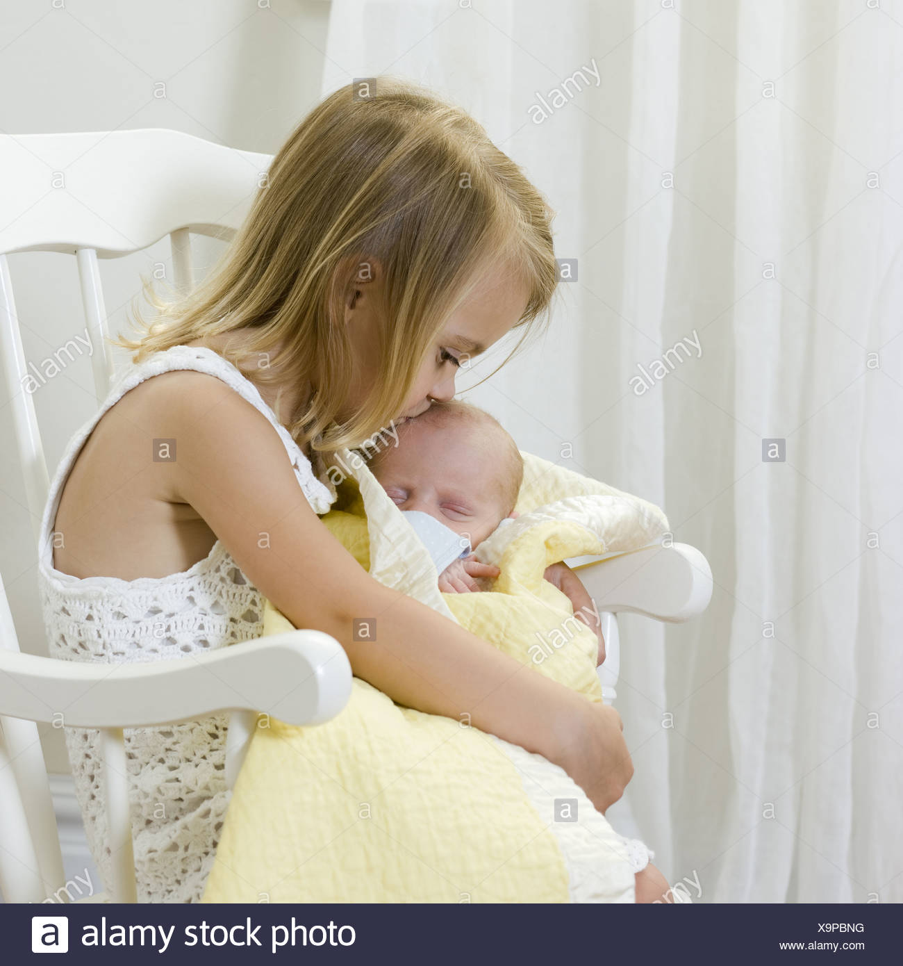 big sister holding her newborn brother Stock Photo