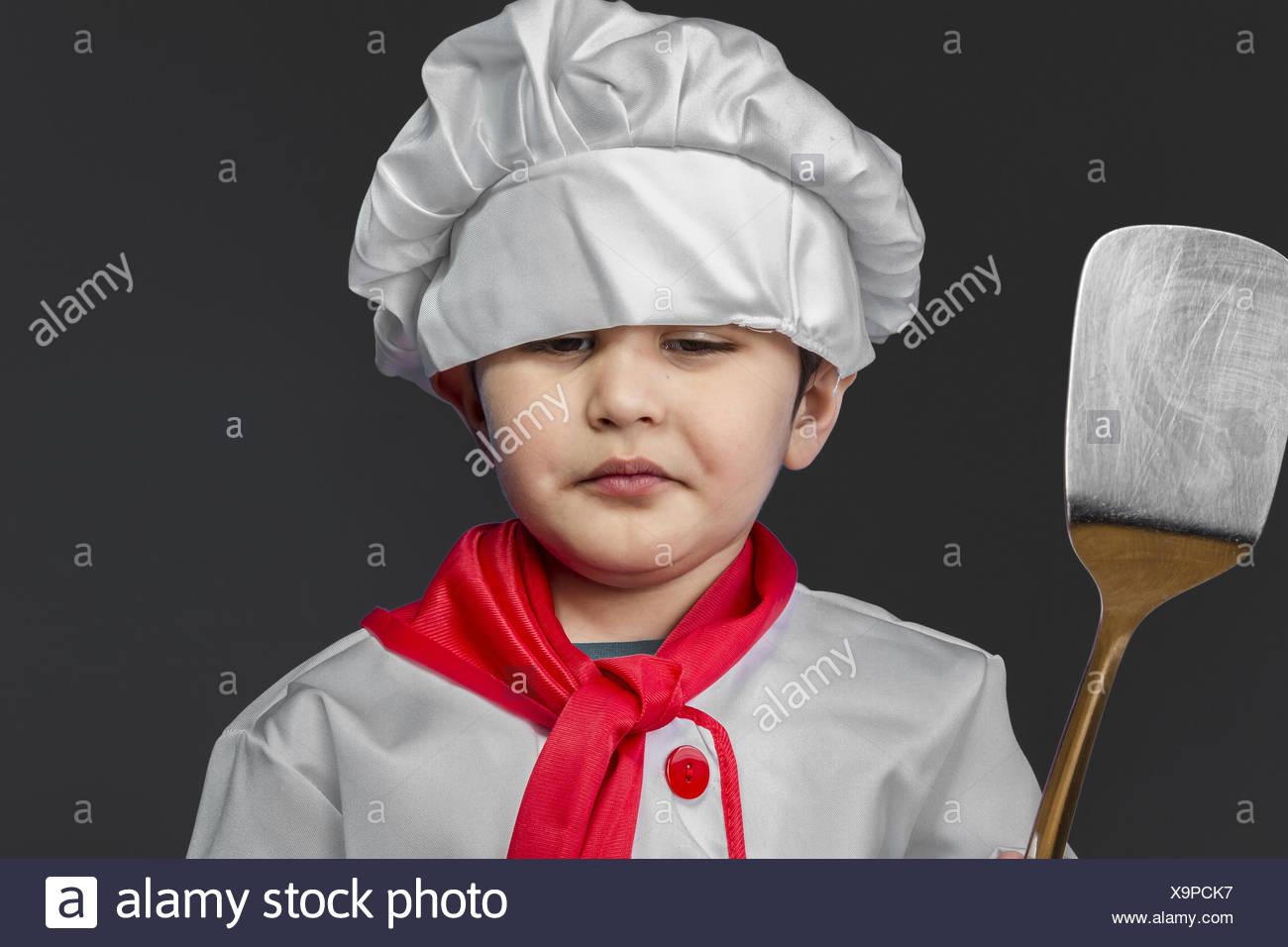Kitchen, little boy preparing healthy food on kitchen over grey background, cook hat - Stock Image