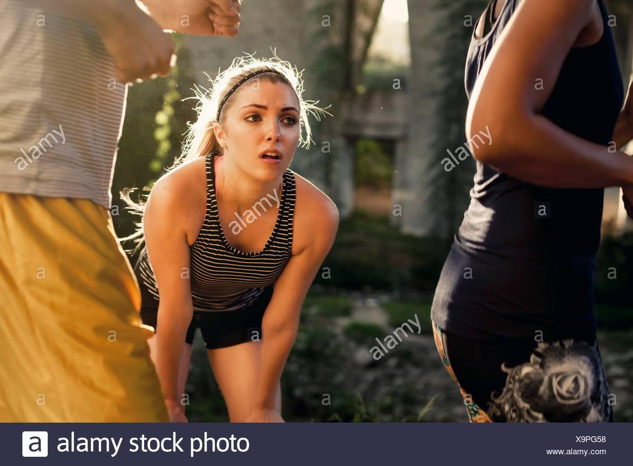 Joggers running past jogger taking break, Arroyo Seco Park, Pasadena, California, USA - Stock Image