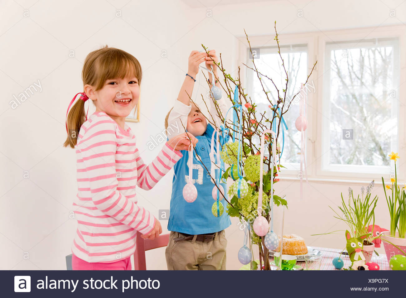 girl and boy decorate easter table - Stock Image